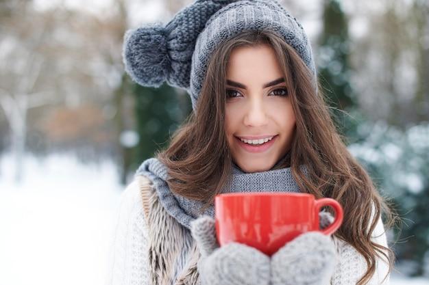 Opwarmen van prachtige jonge vrouw in de winter