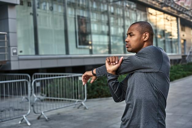Opwarmen voor de training close-up van atletische afrikaanse man die zijn armen strekt voor cardio