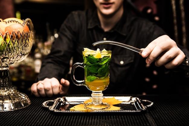 Opwarmende alcoholische cocktail met munt, honing, siroop, mandarijnpot op het aanrecht, op een donkere tafel. sangria, punch