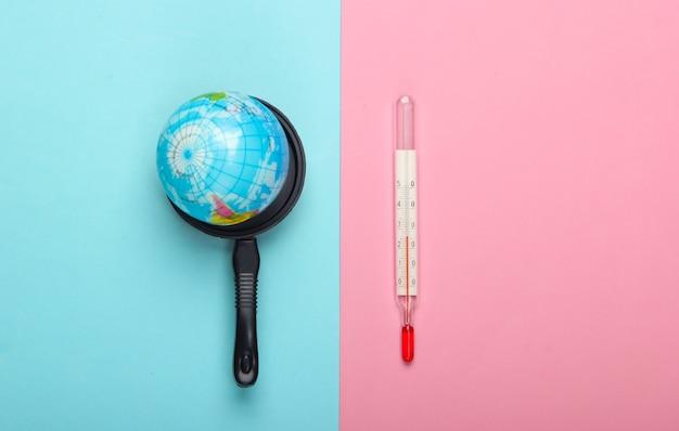 Opwarming van de aarde concept. minibol in een speelgoedpan en thermometer op blauw-roze pastelkleurige muur minimalisme. klimaatproblemen van onze tijd. bovenaanzicht