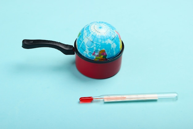 Opwarming van de aarde concept. minibol in een stuk speelgoed pan en thermometer op blauwe muur minimalisme. klimaatproblemen van onze tijd.