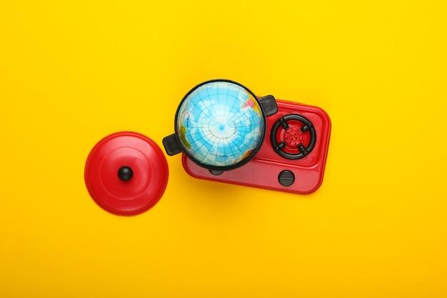 Opwarming van de aarde concept. minibol in stuk speelgoed pan op fornuis. gele muur bovenaanzicht. minimalisme. klimaatproblemen van onze tijd. bovenaanzicht