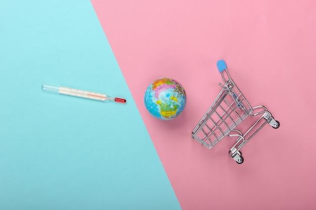 Opwarming van de aarde concept. winkelwagen met thermometer en globe op blauw-roze pastel achtergrond. bovenaanzicht, minimalisme