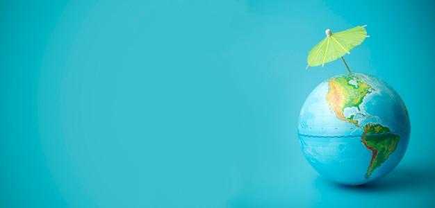 Opwarming van de aarde en klimaatverandering op aarde concept. earth globe met een paraplu. bescherming van de atmosfeer tegen ultraviolette straling en ozongaten
