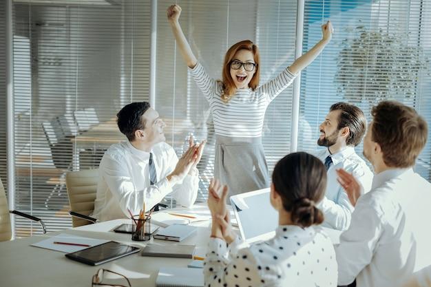 Opwindend nieuws. vrolijke jonge vrouw viert het ontvangen van goed nieuws tijdens de ontmoeting met haar collega's, triomfantelijk haar handen opheffend