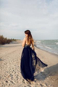 Opwindende gracieuze vrouw in elegante lange blauwe jurk gek rond en plezier op het tropische strand. vakantietijd
