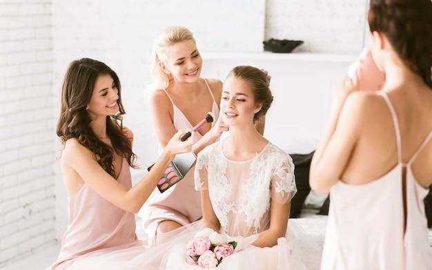 Opwindende sfeer. opgetogen glimlachende jonge bruidsmeisjes die in de witte slaapkamer zitten terwijl ze de bruid helpen zich voor te bereiden en geluk te uiten