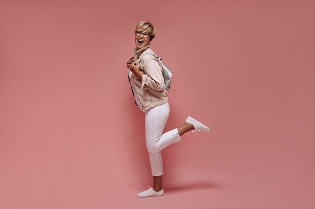 Opwindende vrouw met blond haar en coole bril in witte broek en stijlvolle jas lachen op geïsoleerde roze achtergrond.