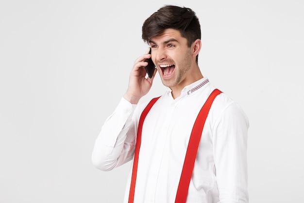 Opwinding en verwondering. positieve man praten aan de telefoon, zegt wow, kijkt opzij met ogen vol geluk