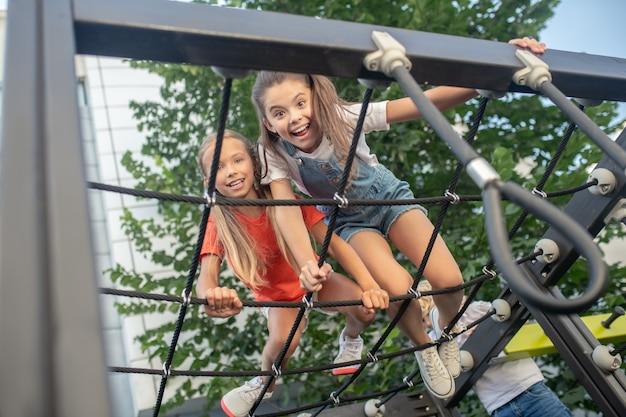 Opwinding. meisjes hebben plezier in de klimrek en voelen zich opgewonden