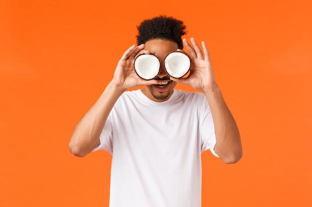 Opwinding, vakantie en vakantie concept. geamuseerde en verraste afro-amerikaanse hipster-man met afro-kapsel, bril maken van kokosnoten op ogen, glimlachend verbaasd, staande oranje achtergrond.
