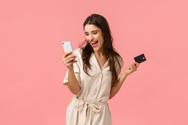 Opwinding, winkelen en vakantie concept. vrolijke en zorgeloze glimlachende mooie vrouw die online aankoop doet, die voor internetlevering betaalt, kan niet wachten ontvang product, houd creditcard en smartphone
