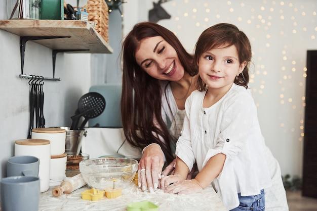 Opzij kijken terwijl de vrouw lacht. gelukkige dochter en moeder bereiden samen bakkerijproducten. kleine helper in de keuken.