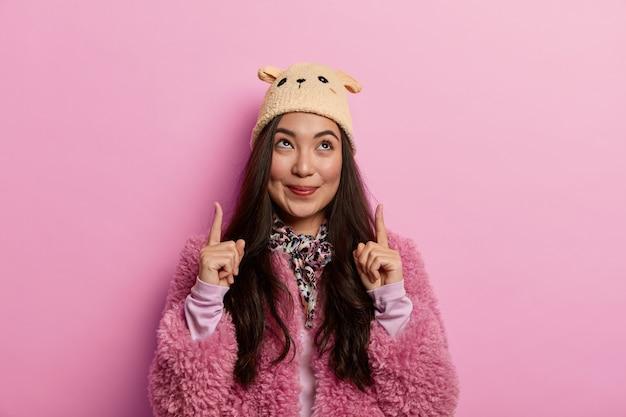 Opzoeken. aantrekkelijke brunette vrouw wijst wijsvingers omhoog, demonstreert cool item met aangename tedere glimlach, draagt roze jas