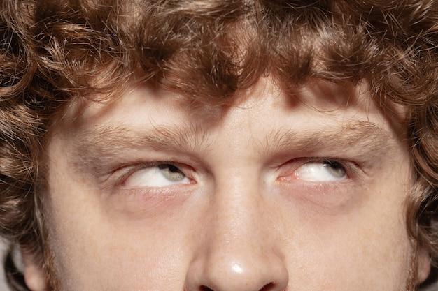 Opzoeken. close-up van het gezicht van een mooie blanke jongeman, focus op de ogen.