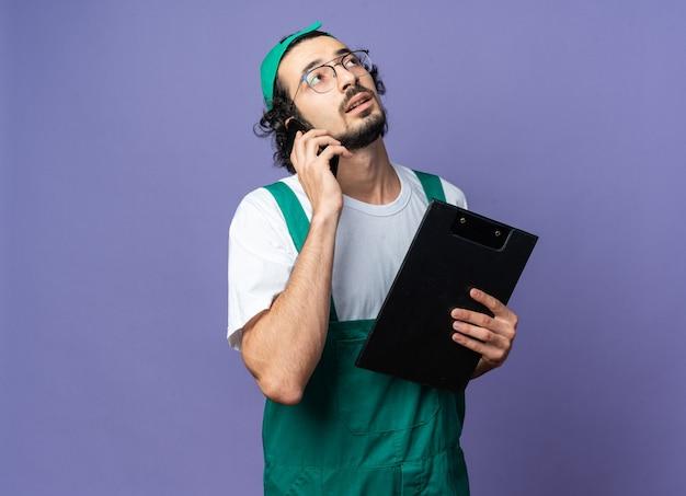Opzoeken van jonge bouwer man met uniform met pet spreekt op telefoon met klembord