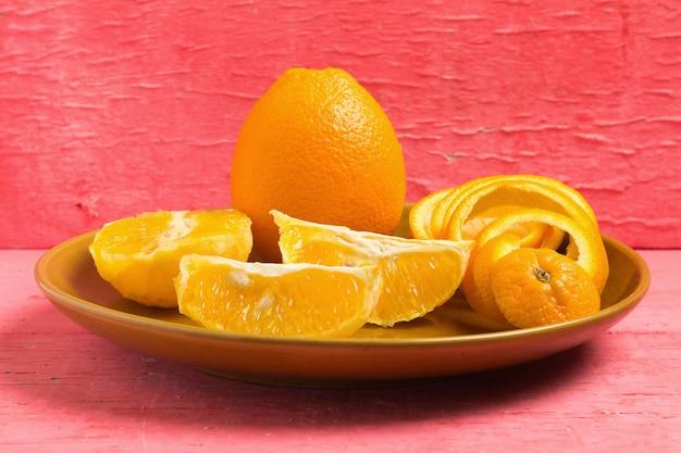 Orange spiral peel half slice on dish on pink wood