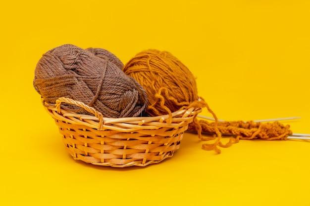 Oranje achtergrond, bruine en okerkleurige draden om in een mand te breien, naast het breien begonnen op de naalden