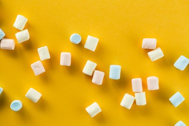 Oranje achtergrond met kleurrijke marshmallows