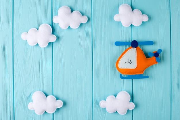 Oranje ambachtshelikopter en wolken op blauwe houten achtergrond met copyspace. voelde handgemaakte speelgoed.