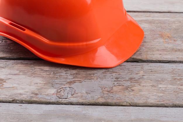 Oranje arbeidershelm op de oude houten tafel. sluit de pet van de constructeur af.