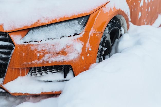 Oranje auto staat op parkeerplaats, bedekt met witte sneeuw, vast na zware sneeuwval in de stad