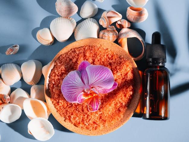 Oranje badzout in een schotel met schelpen en bloem op een blauwe achtergrond met een schaduw van een tropische plant. copyspace, flatlay. spa, ontspannen, zomer