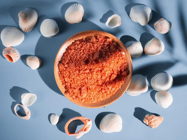 Oranje badzout in een schotel met schelpen op een blauwe achtergrond met een schaduw van een tropische plant. copyspace, flatlay. spa, ontspannen, zomer