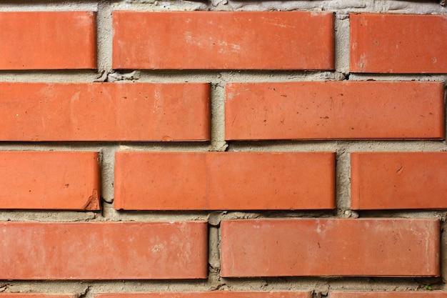 Oranje bakstenen muur met ongelijk vuil metselwerk grijs cement.