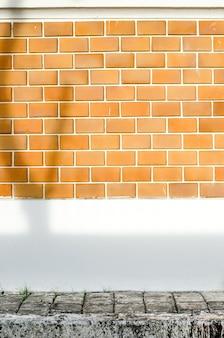 Oranje bakstenen muur met witte cement geschilderde muur en bestrating en boomschaduw