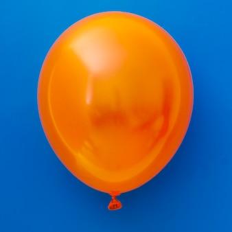 Oranje ballon op blauwe achtergrond
