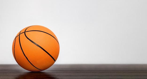 Oranje basketbalbal in de sporthal op onscherpe achtergrond. kopieer ruimte
