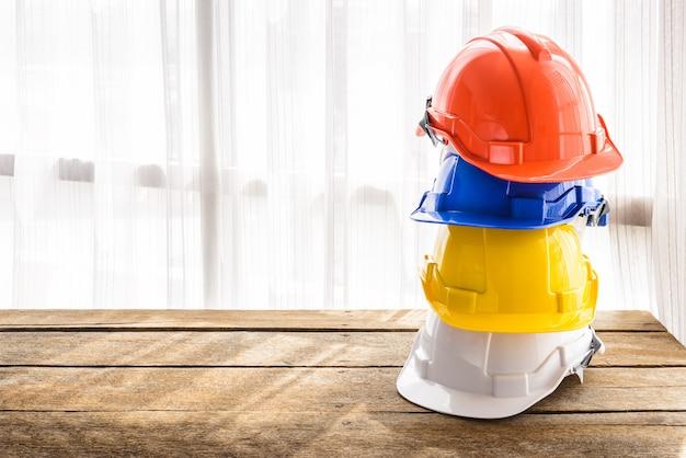 Oranje, blauwe, gele, witte harde veiligheidshelm bouwhoed voor veiligheidsproject van arbeider als ingenieur of arbeider