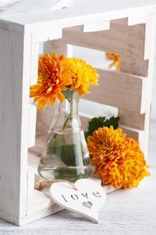 Oranje bloemen in glazen pot op rustieke tafel