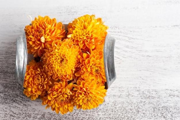 Oranje bloemen in vak op rustieke tafel