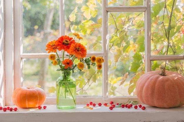 Oranje bloemen met pompoenen op wit venster