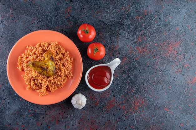 Oranje bord fusilli pasta met kippenvleugel op marmeren oppervlak.