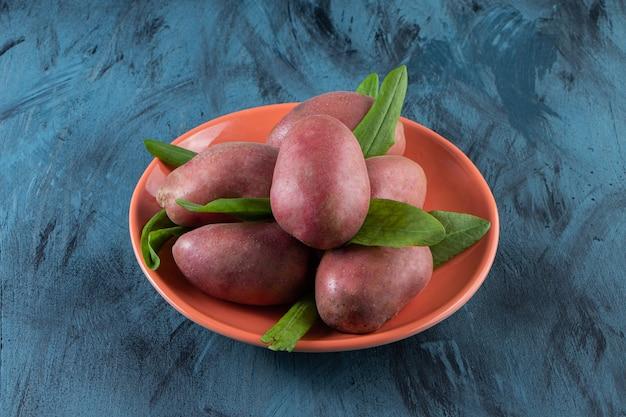 Oranje bord met zoete biologische aardappelen op blauwe ondergrond.