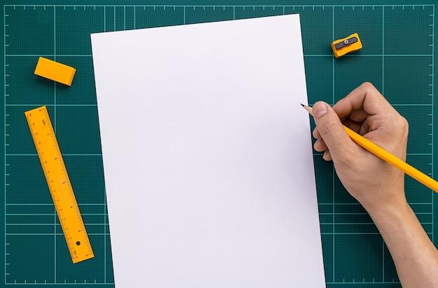 Oranje briefpapier en rechterhand op groene snijmat