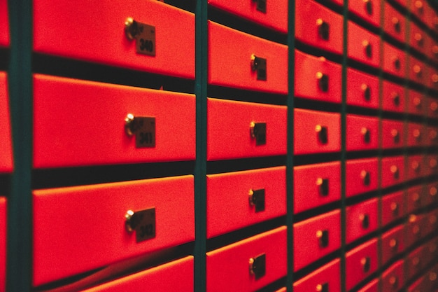 Oranje brievenbussen in een flatgebouw. even rijen genummerde brievenbus. correspondentieconcept in de stad. je kunt het gebruiken als achtergrond voor je advertentie. ruimte kopiëren