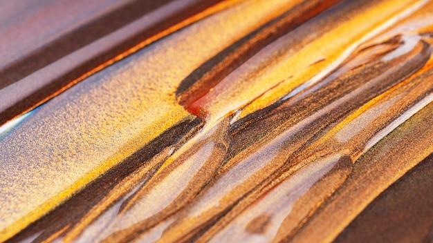 Oranje bruine achtergrond met glinsterende uitstrijkjes. abstracte verf textuur. creatieve penseelstreken van goudverf. make-up concept. feestelijke achtergrond