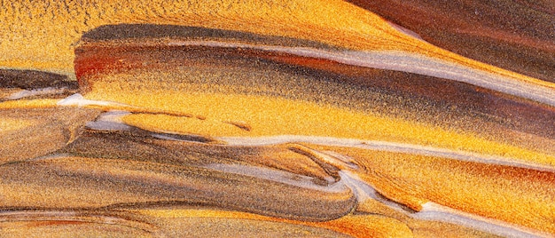 Oranje bruine achtergrond met glinsterende uitstrijkjes. abstracte verf textuur. feestelijke achtergrond