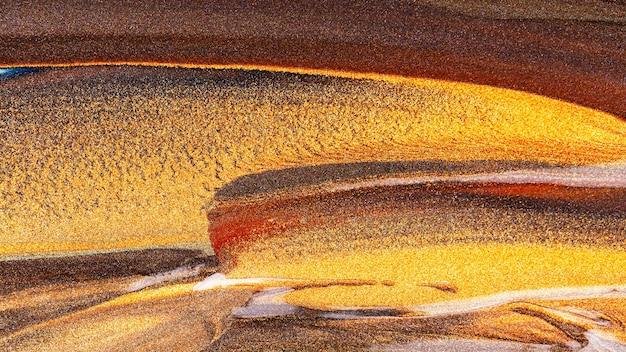 Oranje bruine achtergrond met glinsterende uitstrijkjes. abstracte verf textuur