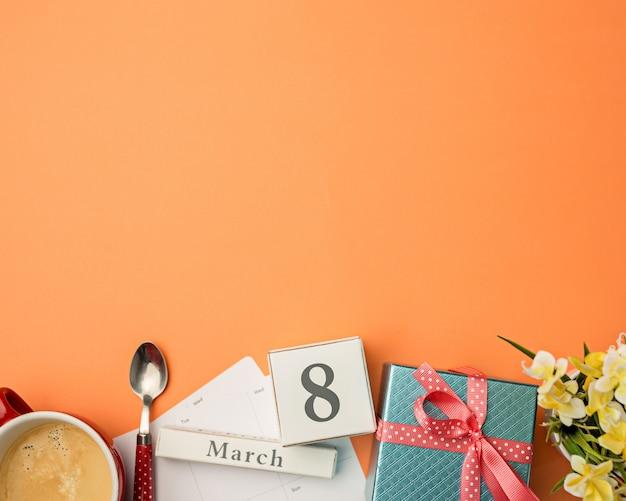 Oranje bureau met kopje koffie, cadeau, bloemen en laptop