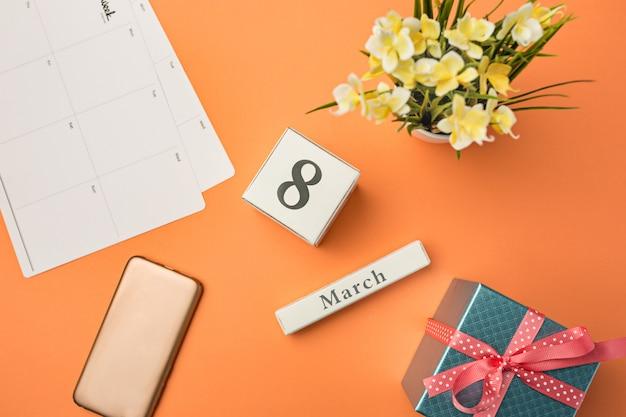 Oranje bureau met telefoon, cadeau, bloemen en laptop