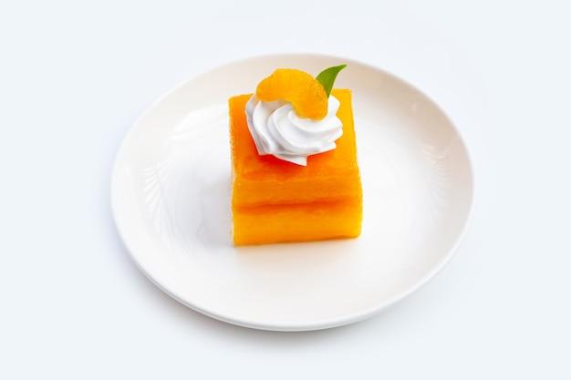 Oranje cake in witte plaat op witte achtergrond.