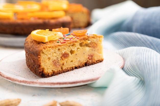 Oranje cake met amandelen en een kopje koffie op een witte betonnen achtergrond en blauw linnen textiel. bovenaanzicht, close-up,