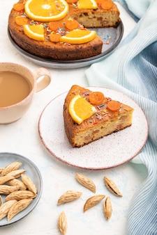 Oranje cake met amandelen en een kopje koffie op een witte betonnen achtergrond en blauw linnen textiel.