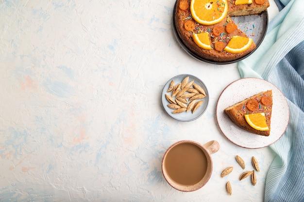 Oranje cake met amandelen en een kopje koffie op een witte betonnen tafel en blauw linnen textiel. bovenaanzicht, plat leggen, kopie ruimte.