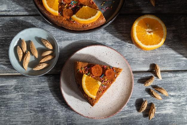 Oranje cake op een grijze houten achtergrond. hard licht. contrast, low key. bovenaanzicht, platliggend,